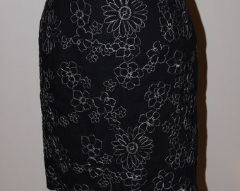 Black, white embroidered, lined pencil skirt.  Size medium.  Knee length. Center back invisible zipper above a walking slit at the hem.