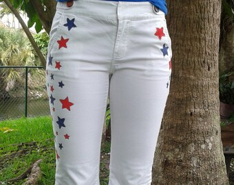 4th of july holiday, patriotic embellishd jeans.  White jeans hand painted with red and blue stars that are outlined with glitter.