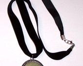 large gray-green stone pendant on velvet ribbon