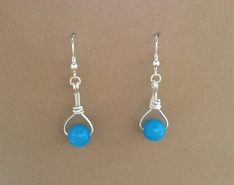 Sterling silver dangle earrings with light blue onyx bead.