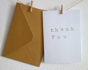 "Card ""thank you"". Hand stamped with gold-coloured ink. Folded, blank inside, with gold-colouredenvelope,"