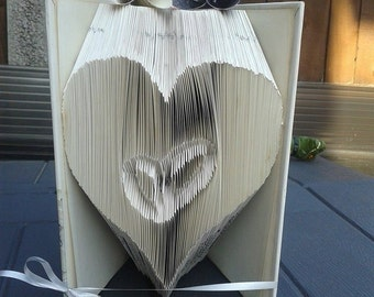 Book folding art pattern for a heart with wedding rings inside