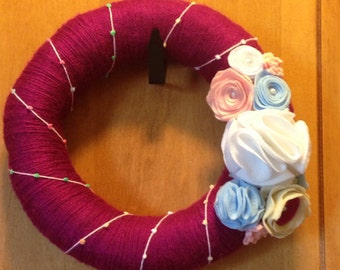 Pink yarn wreath with felt flowers.