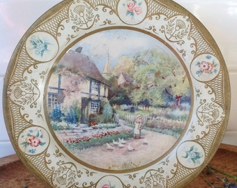 "Tin ""willow"" make plate with rustic coloured country image on front."