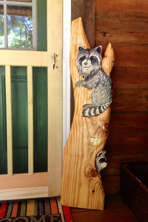 Raccoons in tree chainsaw wood raccoon carving by