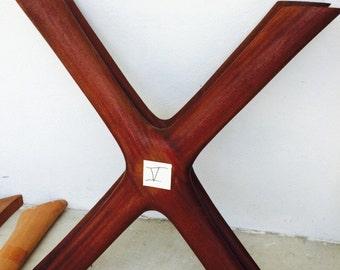 Custom sculptural hardwood trestle table legs.