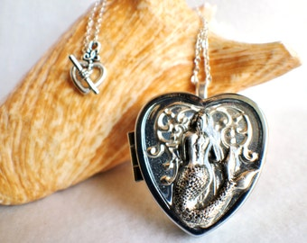 Music box locket, heart shaped locket with music box inside, in silvertone with mermaid on front cover.