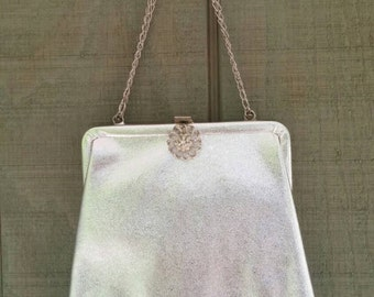 Metallic silver vinyl evening bag with chain handle and rhinestone clasp, 1960s