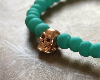 Aqua Rose Skull: an elastic beaded bracelet with rosegold skull and matte turquoise / teal glass beads.