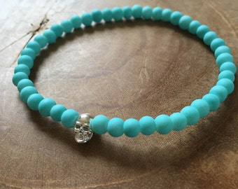 Blue Silver Skull: an elastic beaded bracelet with silver skull and matte lightblue glass beads.