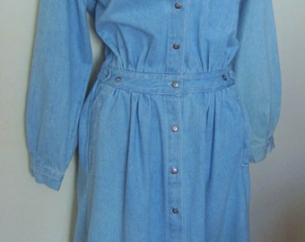Vintage faded blue 80's -90's denim dress.The dress has a shirt style motif with a 13 button front closure. Long sleeves, gathered at waist.