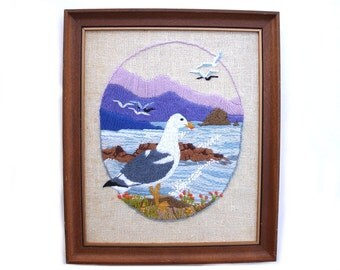 Vintage seagull artwork, needlework bird art, seascape crewel embroidery, sea gull at shore purple mountains, waves rocky shore