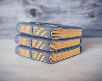 Pocket-sized handmade leather journal with with soft gray cover and yellow pages