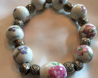 Asian style bracelet with pink porcelain beads and an oval focal bead wirh silvertone beads-stretch