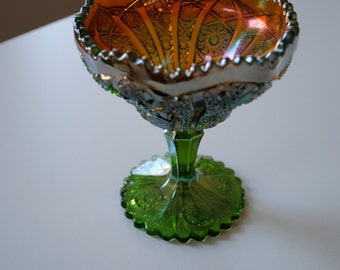 a vintage ice cream sundae glass dish. ornate accented in multiple colors and a green base.