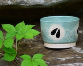 Small light green bowl with deer hoof prints