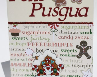 A festive Merry Christmas greeting card in Chamorro. Gingerbread house and gingerbread men add a fun feel.
