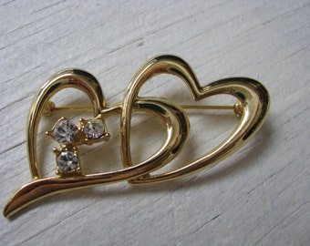 Vintage gold tone double heart pin with rhinestone accents