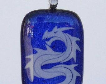 Enamel White dragon on dichroic blue glass pendant.