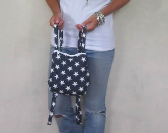 Small backpack purse in navy with white stars. Zipper closure and adjustable straps.