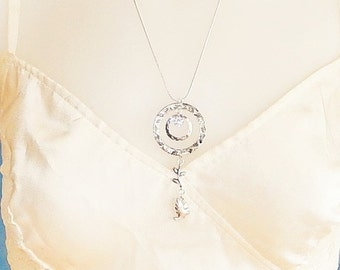 Silver necklace with a hammered circle pendant a Crystal charm a bird charm and a Branch charm hung on a silver tone chain, Crystal necklace