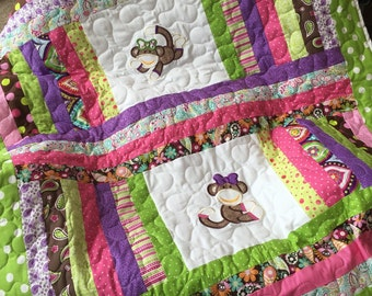 Lime green, pink, brown, and purple baby girl sock monkey quilt