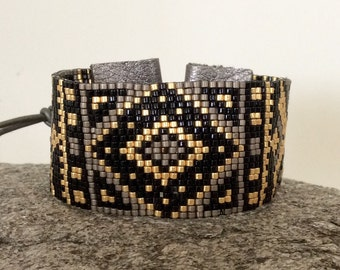 Beaded bracelet in Geometric pattern, width is 30mm with an adjustable closure.