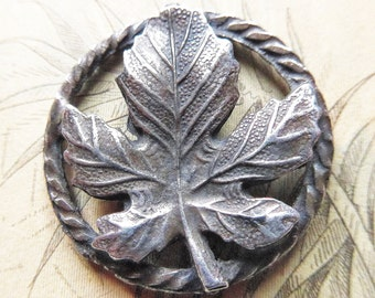 Leaf button, vintage, cut, pressed metal, a leaf suspended on a twisted border.  c1940's-50's thereabouts.