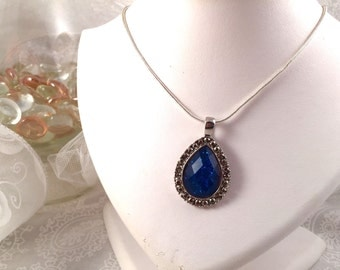 Silver-tone chain necklace, with ornate blue faceted tear-drop pendant