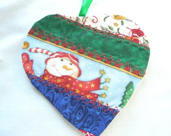 Christmas ornament  heart shape, snowman, Christmas prints, strip sewing, decorative top stitching in red, 4 1/2 by 4 1/2 inches.