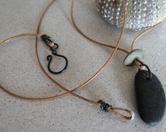 very simple necklace for men or women. Small grey pebbles with a cute linen pouch.
