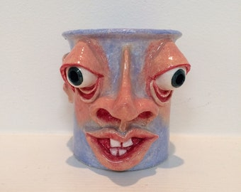 A hand built, individually sculpted, hand painted face pot in a baby blue color.