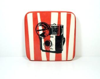 tile with a kodak starmite camera on various asymmetrical red-orange stripes, made to order.