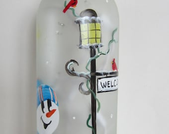 Frosted Lighted Bottle With a  Snowman At the Lamp Post and a Welcome Sign