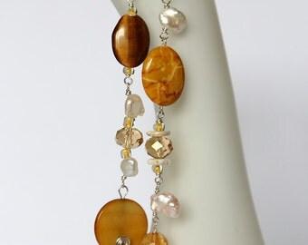 Very long brown asymmetrical golden sand earrings, white keshi pearls, tigers eye, shell, orange golden brown fashion statement earrings