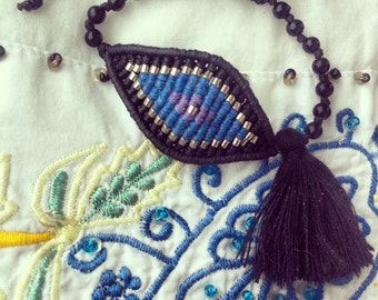Large evil eye macrame bracelet in black, silver, light blue and lilac colors with a black tassel.