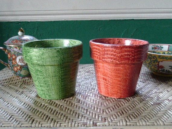 A pair of flowerpots vinegar painted in sienna and green