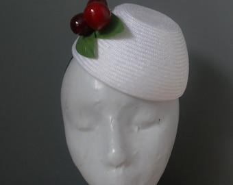 White straw hat with cherry trim.