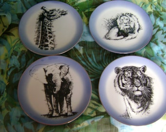 Four wild animal plates.Majestic,yet sensitive portraits in black on white china ground,fading to blue rim with gold edge