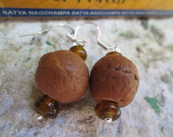 Earrings. Materials: seed of the Bodhi tree, amber, steel, silver.