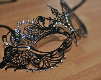 Black metal lightweight masquerade venetian mask with diamonte finishes.Filigree styling with black silk ties.