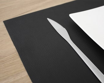 Together of 4 design place mats in black imitation leather