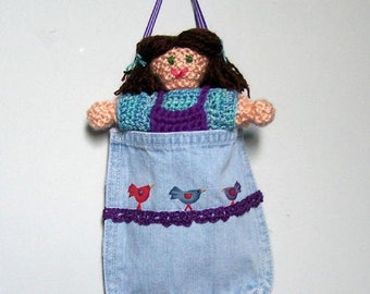 Knit doll in overalls in a recycled denim pocket