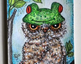 Artist trading card of cute whimsical owl dressed in a childs frog hat.