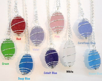Eco Friendly Recycle Sea Glass wrap around with silver plated wire cage on a silver plated necklace chain.