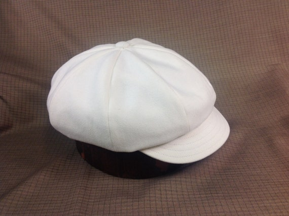 Flat top 8 panel cotton pageboy cap. Brushed cotton twill with white cotton lining. Leather or cotton sweatband, fitted to any size.