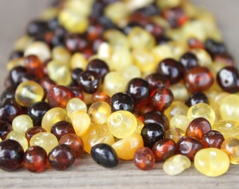 50 pcs Polished colored Baltic amber beads with drilled hole.