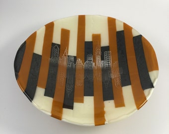 Brunt orange, iridescent gold and creme strips with shadow of a city skyline fused glass footed bowl
