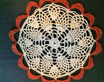 Vintage crocheted ecru and rust colored doily