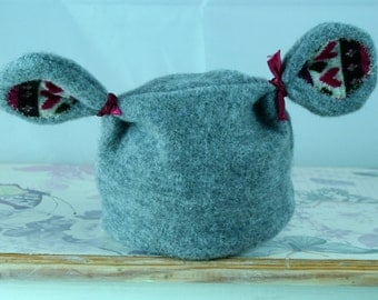 A handmade cute newborn baby hat made with soft grey cotton jersey fabric.